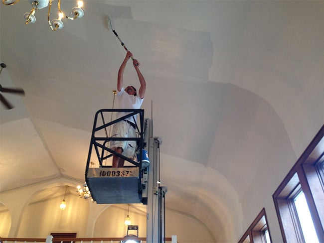 painter on a lift painting the ceiling