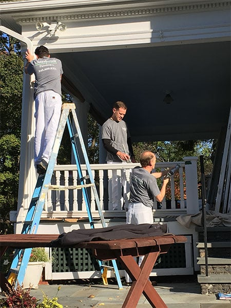 family crew photo of them working on painting a porch