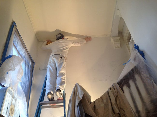 professional painter reinstalling crown molding for painting